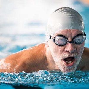 Senior man swimming in an indoor swimming pool. Active pensioner enjoying sport.